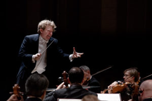 Conductor gestures while directing a symphony orchestra
