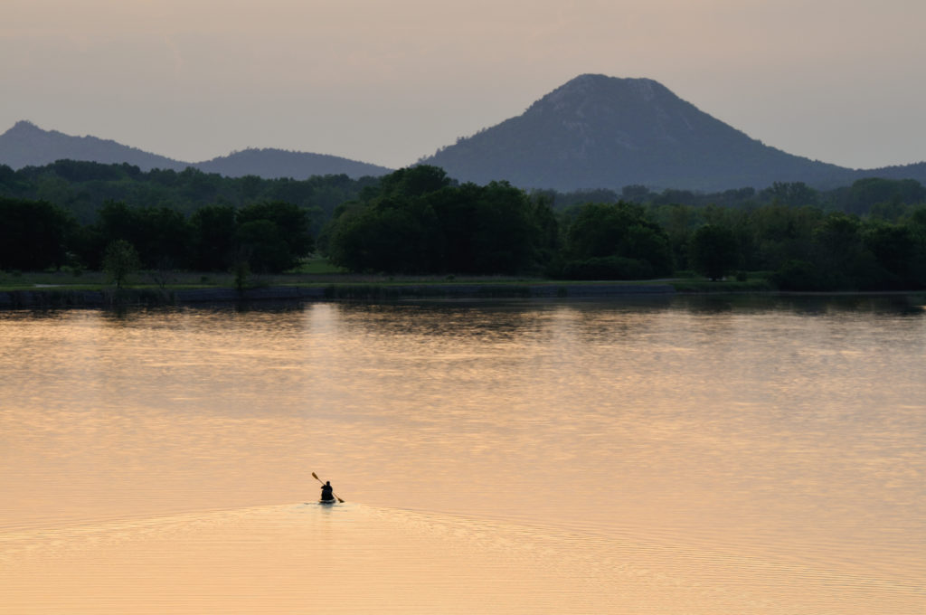 Lone person canoeing on a lake at sunset or sunrise with mountain in the background.
